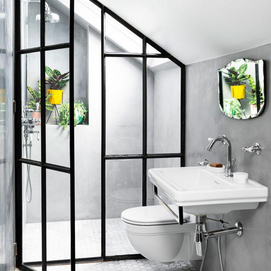 Lichtgrijze kalkverf aan de muren in deze kleine badkamer zorgt voor ruimtelijkheid.