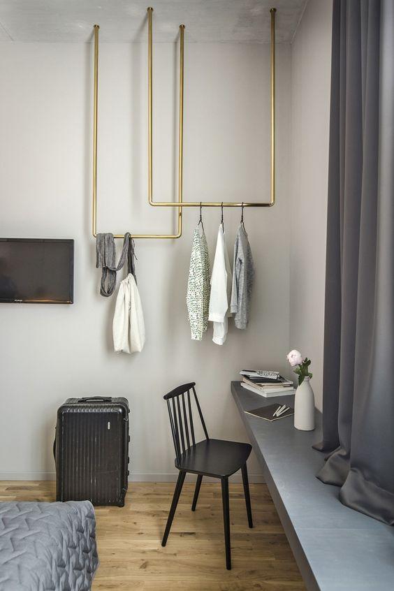 Gouden kledingrek aan plafond slaapkamer