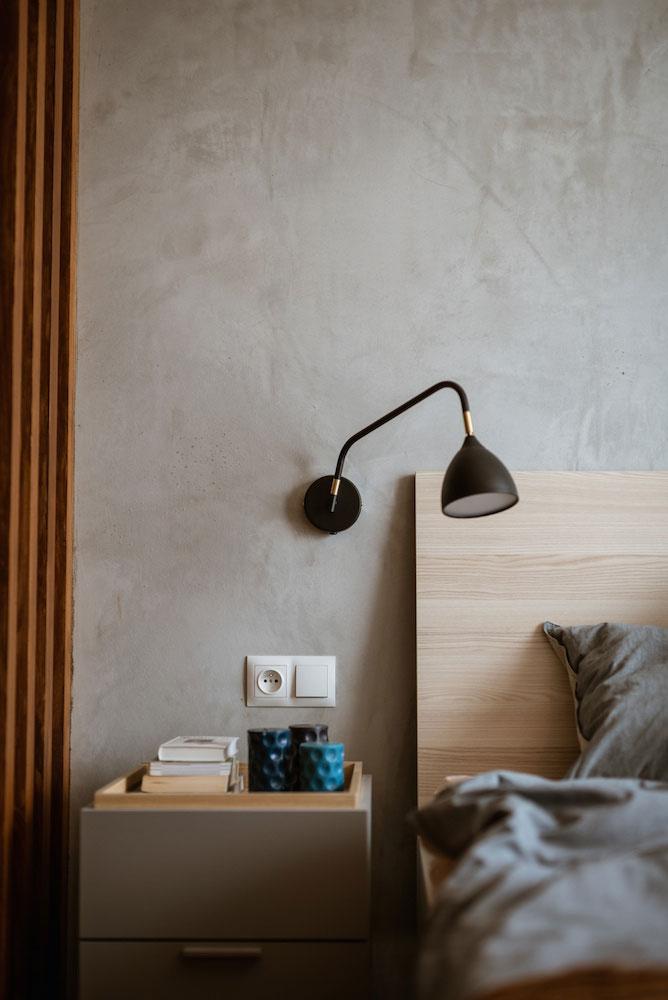 In deze slaapkamer scheidt een scheidingswand van houten latten de inloopkast van het bed