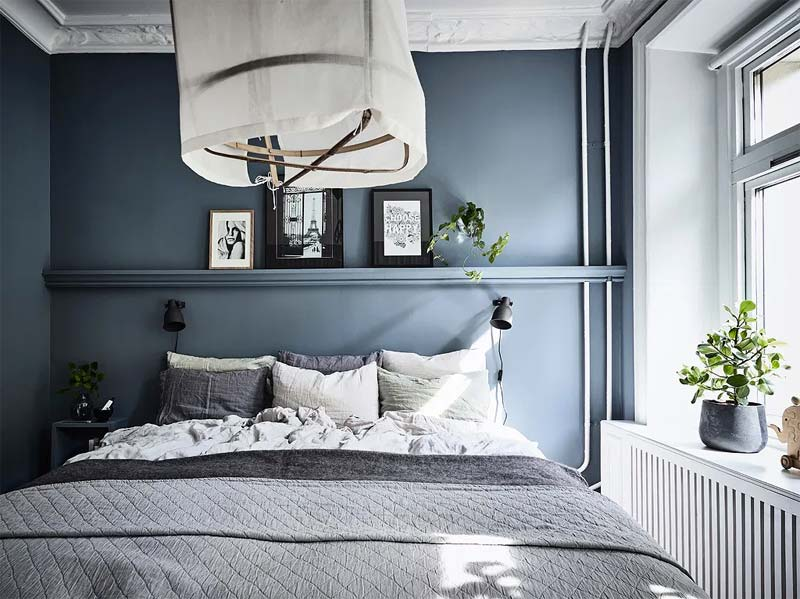 De smalle wandplank boven het bed in deze kleine slaapkamer is met de muur meegeschilderd.